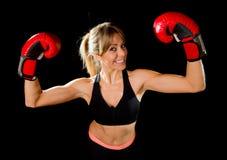 有拳击手套的年轻愉快的美丽的拳击手女孩在胜利标志武装用适合和健康身体 免版税库存图片