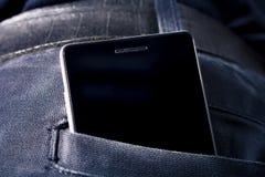 有拷贝空间的黑智能手机在黑暗的裤子后面口袋 库存照片