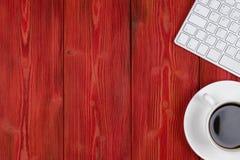 有拷贝空间的办公桌 数字式设备无线键盘和老鼠在红色木桌上与咖啡,顶视图 免版税库存照片
