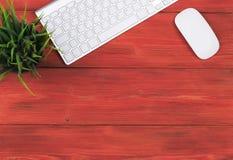 有拷贝空间的办公桌 数字式设备无线键盘和老鼠在红色木桌,顶视图上 库存图片