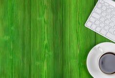 有拷贝空间的办公桌 数字式设备无线键盘和老鼠在绿色木桌上与咖啡,顶视图 免版税图库摄影
