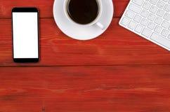 有拷贝空间的办公桌 数字式设备有空的屏幕的无线键盘、老鼠和片剂计算机在红色木桌w上 免版税库存图片