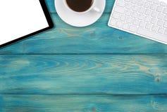 有拷贝空间的办公桌 数字式设备有空的屏幕的无线键盘、老鼠和片剂计算机在蓝色木桌上 库存图片