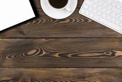 有拷贝空间的办公桌 数字式设备有空的屏幕的无线键盘、老鼠和片剂计算机在黑暗的木桌上 库存图片