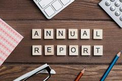 有拼写年终报告的办公室材料和木立方体的企业工作场所 库存照片