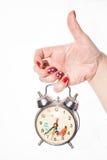 有拿着一个减速火箭的时钟的红色钉子的手指,白色 库存图片