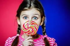 有拿着一个大五颜六色的焦糖糖果的美丽的嫉妒的小女孩 图库摄影