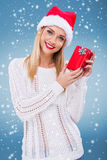 有拿着一个小红色礼物盒的圣诞老人帽子的美丽的妇女 免版税库存图片