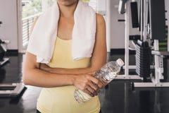 有拿着一个瓶水的白色毛巾的健身妇女 库存照片