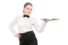 有拿着一个空的盘子的蝶形领结的一位女服务员 免版税图库摄影