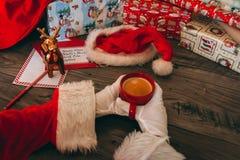 有拿着一个红色杯子用咖啡的白色手套的圣诞老人 图库摄影