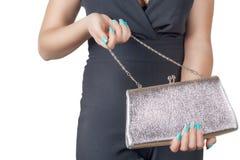 有拿着一个银色提包的蓝色修指甲的女性手 免版税库存图片