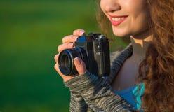 有拿着一台老照相机的卷发的美丽的女孩摄影师和在公园拍一张照片,在春天户外 库存图片