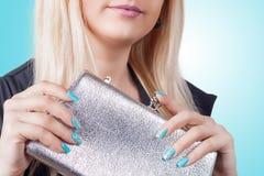 有拿着一台银色传动器的蓝色修指甲的妇女 库存照片