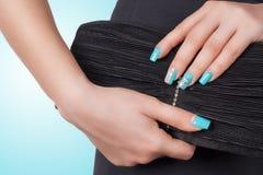 有拿着一台黑传动器的蓝色修指甲的女性 库存图片
