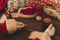 有拿着一支欢乐铅笔和一个红色杯子用咖啡的白色手套的圣诞老人 免版税库存图片