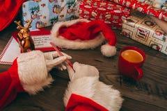 有拿着一支欢乐铅笔的白色手套的圣诞老人 库存照片