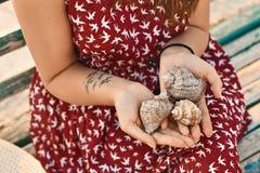 有拿着三个美丽的贝壳的鸟纹身花刺的少妇 免版税库存图片