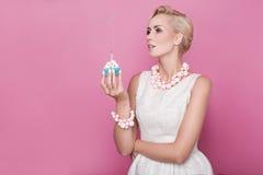 有拿着与五颜六色的蜡烛的奶油色礼服的美丽的妇女小蛋糕 生日,假日 免版税库存照片
