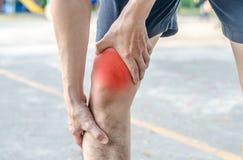 有拿着与他的强的运动腿的年轻体育人膝盖 库存照片