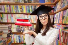 有拿着书的毕业盖帽的惊奇的学生 免版税图库摄影