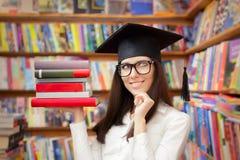 有拿着书的毕业盖帽的愉快的学生 免版税库存照片