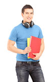 有拿着书的耳机的一名英俊的学生 图库摄影
