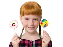 有拿着五颜六色的糖果的雀斑的小可爱的红发女孩 库存照片