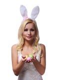 有拿着五颜六色的鸡蛋的兔宝宝耳朵的复活节妇女 图库摄影