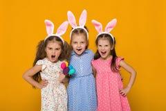 有拿着五颜六色的鸡蛋的复活节兔子耳朵的女孩 免版税库存图片