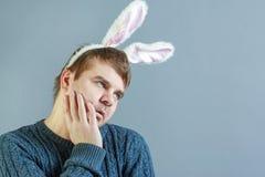 有拿着他的面颊的兔宝宝耳朵的不剃须的人 一个人以宿酒,在假日以后 奇怪的纵向 图库摄影