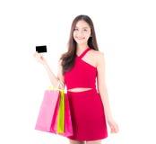 有拿着信用卡和袋子纸的红色礼服的亚裔少妇 图库摄影