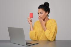 有拿着信用卡的膝上型计算机的震惊妇女 图库摄影