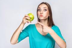 有拿着和吃苹果和指向和看与大眼睛的雀斑和绿色礼服的年轻美丽的妇女照相机 免版税库存图片