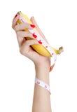 有拿着和测量香蕉的红色钉子的性感的妇女手 库存图片
