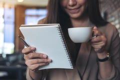 有拿着和看一个白色空白的笔记本的兴高采烈的面孔的一名美丽的亚裔妇女,当喝在现代咖啡馆时的咖啡 免版税图库摄影