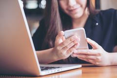 有拿着和看巧妙的电话的兴高采烈的面孔的一名美丽的亚裔妇女,当使用在木桌上时的膝上型计算机 免版税库存图片
