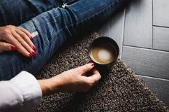 有拿着咖啡在膝盖的红色钉子的妇女的手,当坐面粉时 免版税库存照片