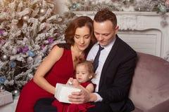 有拿着圣诞节礼物的一个孩子的愉快的年轻家庭 在家坐在圣诞树附近的沙发 库存图片
