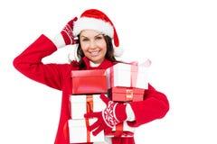 有拿着圣诞节礼物的圣诞老人帽子的美丽的浅黑肤色的男人 免版税库存图片