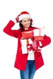 有拿着圣诞节礼物的圣诞老人帽子的美丽的浅黑肤色的男人 图库摄影
