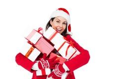有拿着圣诞节礼物的圣诞老人帽子的美丽的浅黑肤色的男人 库存图片