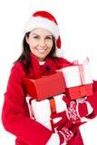 有拿着圣诞节礼物的圣诞老人帽子的美丽的浅黑肤色的男人 免版税图库摄影