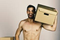 有拿着在他的肩膀的性感的赤裸躯干的人纸板箱 有胡子和惊奇的面孔运载的箱子的强壮男子 免版税图库摄影