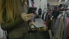 有拿着在商店购物中心的长的头发的俏丽的女孩购物袋和使用她的智能手机发短信给她的朋友- 股票录像
