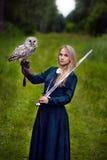 有拿着在她的胳膊的剑的女孩一头猫头鹰 免版税库存图片