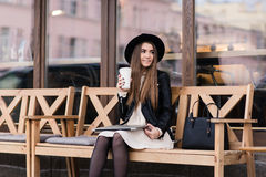 有拿着在她的膝盖的凉快的样式的质朴的妇女闭合的网书,当坐一条舒适长凳在咖啡店窗口附近时 库存图片
