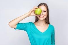 有拿着在她眼睛和微笑前面的雀斑和绿色礼服的年轻美丽的妇女苹果 美丽的夫妇跳舞射击工作室妇女年轻人 免版税库存照片