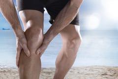 有拿着在痛苦遭受的肌肉伤赛跑的运动腿的年轻体育人膝盖 库存照片
