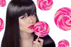 有拿着在swee的桃红色嘴唇的可爱的俏丽的女孩棒棒糖 免版税库存图片